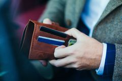 Purse with money in the hands of a man driving a car Stock Images