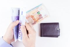 Purse with money in hands. On a white background Royalty Free Stock Photo
