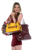 Purse obsession. Woman holding several bags in her hands royalty free stock photos