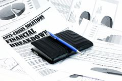 Purse and pen upon newspaper article about crisis Royalty Free Stock Images