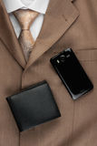 Purse and phone lying on the suit and tie Royalty Free Stock Photography