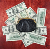Purse placed on center of money dollar and wood background, business concept Stock Photos