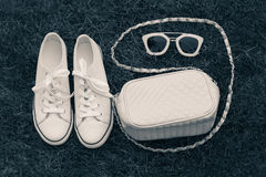 Purse, sneakers and sunglasses with  grass as a background Stock Image