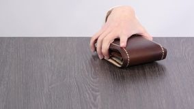 Purse on the table, children`s hand stealing wallet stock footage