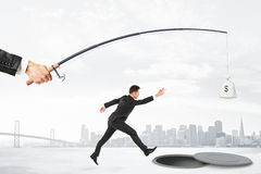 The pursuit of money with businesman jumping into the abyss and Royalty Free Stock Image