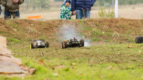 Pursuit. Two remote controlled cars on dirty race track Royalty Free Stock Images