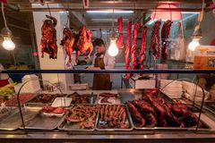 BBQ Duck and Pork purveyor. A purveyor of local BBQ duck, goose and pork hangs his food at the front of his small premises in a Shanghai marketplace royalty free stock photos