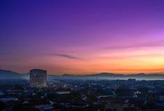 Purwokerto-Stadt bei Sonnenaufgang Schattenbild des kauernden Geschäftsmannes Stockbild