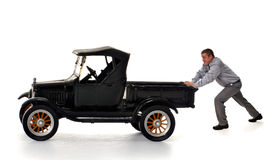 Push!. Man pushing an oversized model of a Model-T truck.  Isolated on white Stock Photos