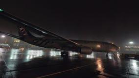 Push-Back all'aeroporto, vista dell'aeroplano alla notte piovosa stock footage