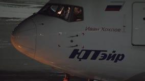 Push-Back dell'aeroplano di Utair alla notte Vista con la cabina di pilotaggio ed il pilota nella cabina archivi video