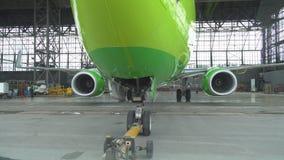 Push-Back di un aereo di linea all'aeroporto in capannone Il naso dell'aeroplano, il carrello di atterraggio e la fine del camion stock footage