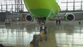 Push-Back di un aereo di linea all'aeroporto in capannone Il naso dell'aeroplano, il carrello di atterraggio e la fine del camion archivi video