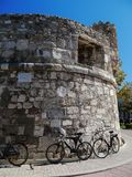 Push bikes waiting for a ride. Push bikes leaning on a old castle frontage Royalty Free Stock Images