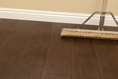 Push Broom on a Newly Installed Laminate Floor and Baseboard. Push Broom on a Newly Installed Laminate Floor and New Baseboards royalty free stock photo