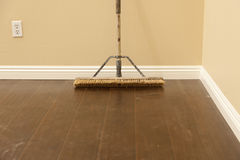 Push Broom on a Newly Installed Laminate Floor and Baseboard Royalty Free Stock Images