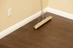 Free Push Broom On A Newly Installed Laminate Floor And Baseboard Royalty Free Stock Photography - 25383737