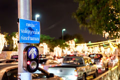 Push button for Red traffic light in Thailand, thai language. Translation: push button wait for walk signal. City road at night. Selective focus, blurred Royalty Free Stock Images