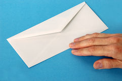 Push the Envelope. Adult hand on the edge of a business size envelope. Business metaphor for taking a risk stock images