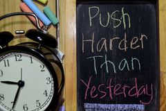 Push Harder Than Yesterday on phrase colorful handwritten on chalkboard. And alarm clock with motivation, inspiration and education concepts. Table background stock photography