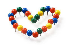 Push index pins. Stationery button pinned to the heart shape Royalty Free Stock Photo