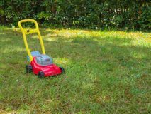 Push lawn mower toy on the grass in a garden . No people. Push lawn mower toy in the middle of a garden in a sunny spring day. No people. Copy space Royalty Free Stock Image