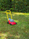 Push lawn mower toy on the grass in a garden . No people. Push lawn mower toy in the middle of a garden in a sunny spring day. No people. Vertical Stock Photo