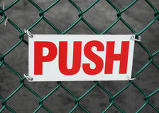 Push. Metal sign reading Push on a chainlink fence stock image