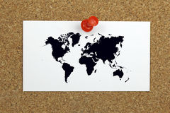 Push pin holding card with world map on a cork board Royalty Free Stock Photography