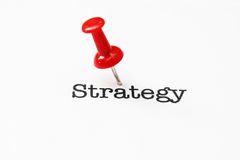 Push pin on strategy text. Close up concept of Push pin on strategy text Royalty Free Stock Images