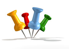 Push Pinning. A collection of 4 differently coloured push pins pierced into a common area Royalty Free Stock Photo