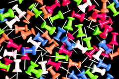 Push Pins. Colorful push pins on black velvet royalty free stock photo