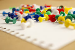 Push Pins on the table. Colorful Push Pins on a white paper sheet Stock Photos