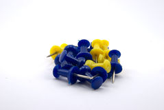 Push-pins on white background. Yellow and blue writing buttons on white buckground Stock Photography