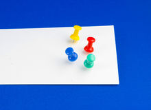 Push pins on white paper. Stock Photo