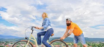 Push and promoting. Impulse to move. Man pushes girl ride bike. Support helps believe in yourself. Feel impulse to start. Moving. Woman rides bicycle sky stock photography