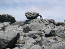 Push the rock. A person trying to push an enormous rock royalty free stock images