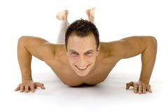 Push up!. Young happy man doing push up exercise. White background in studio royalty free stock photo