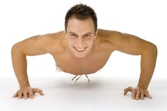 Push up!. Young happy man doing push up exercise. White background in studio stock photo