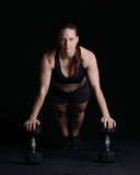 Push Up on Dumbells. Woman doing pushup on two dumbells Stock Image