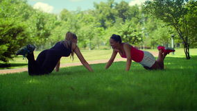 Push up exercise. FItness women doing push ups exercise outdoors. Sporty friends doing pushups fitness training in park. Two girls pushing. Push ups workout at stock video footage
