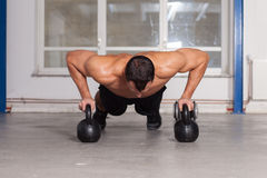Push up on kettlebells crossfit fitness training Stock Images