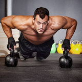 Push up on kettlebells man doing fitness training Stock Photo