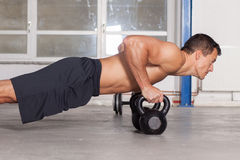 Push up on kettlebells Stock Image