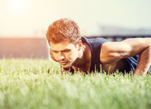 Push up muscular man on green lawn in city park Royalty Free Stock Image