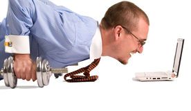 Push-ups. Young businessman doing push-ups with dumbbells, looking on laptop screen stock image