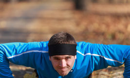 Push-ups. Portrait of a young man doing push-up outdoors in a park in autumn Stock Photography