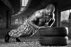 Push-ups. Body builder doing push-ups outdoor on car tires Stock Images