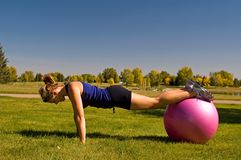 Push ups. Young woman doing push ups with an exercise ball stock photography