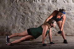 Push-ups During Boot Camp Workout. Boot camp training instructor helping lady with push-ups Royalty Free Stock Photography